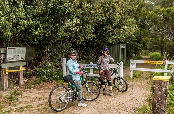 Two women with bicycles entering the North East rail trail