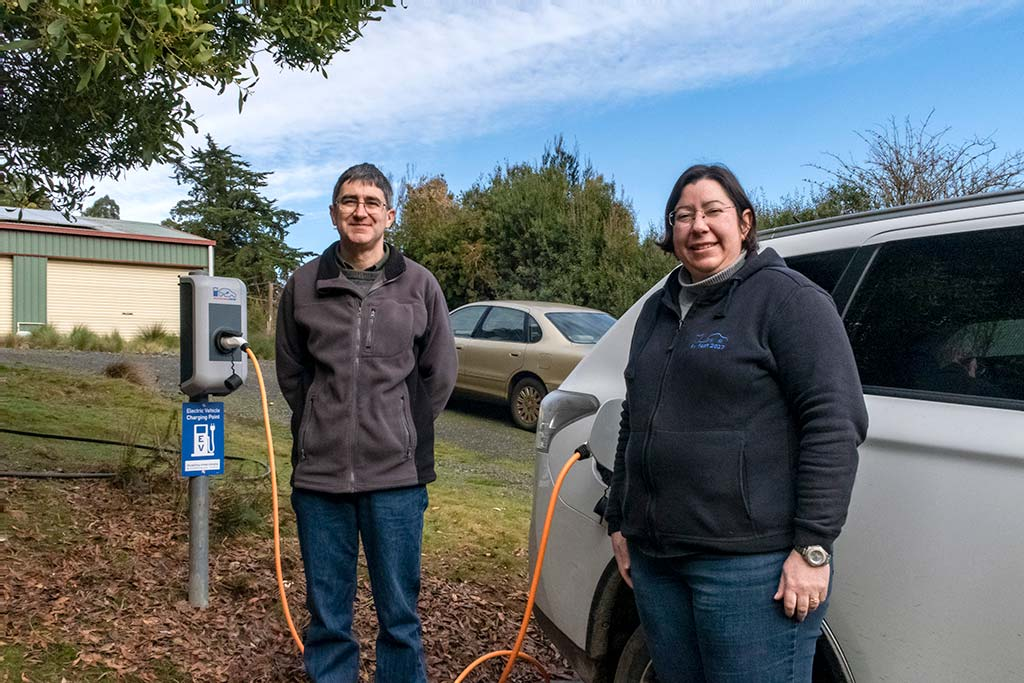 A man an woman who were guests at Tin Dragon Cottages have their car plugged into the Keba EV charging station
