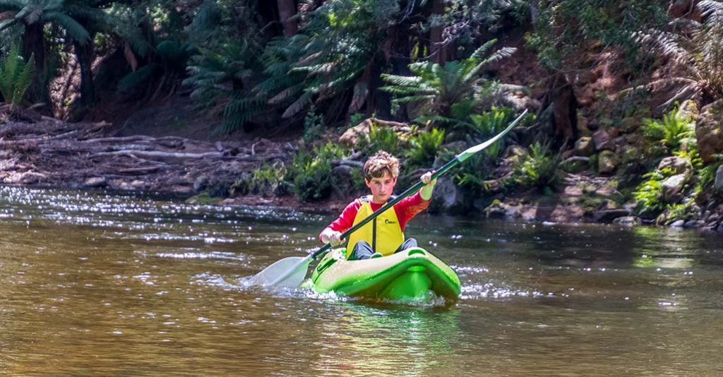Teenage boy kayaking down the Ringarooma River on a family holiday in Tasmania - at Tin Dragon Cottages