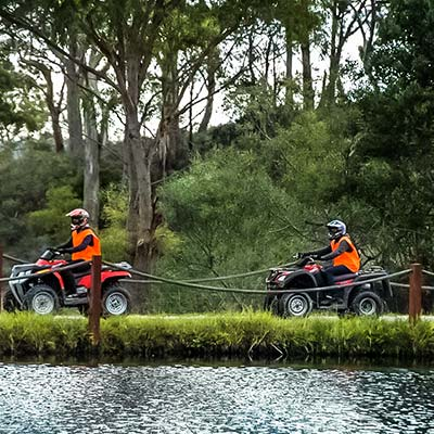 Two people each on quad bikes riding beside a farm dam.