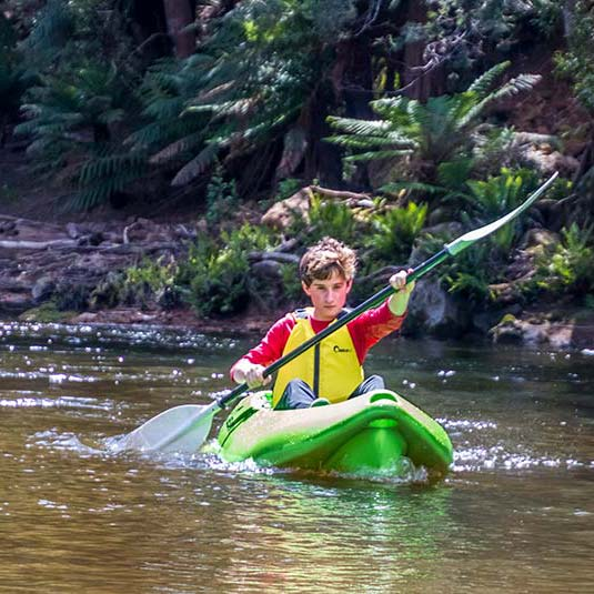 Young teenager kayaking down the Ringarooma River.