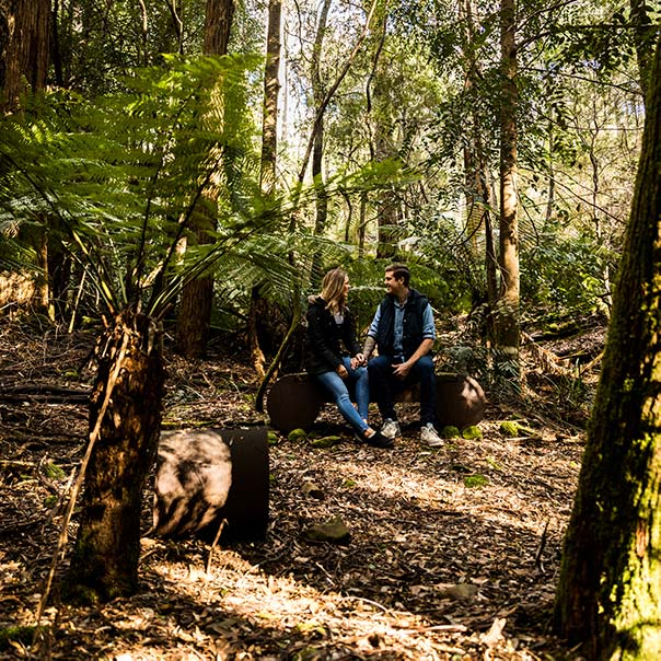 A young couple sit on a sandstone bench in the centre of the heritage Ah Ping mine.