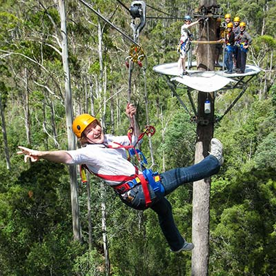 A woman flying between two tree-top platforms on a zip-line.