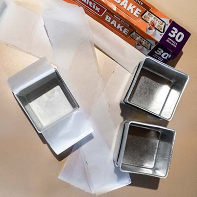 Strips of baking paper and three baking tins on a table.