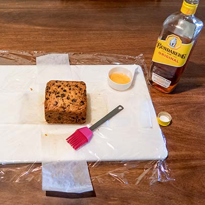One cake is sitting on a white board next to a basting brush and a bottle of rum.