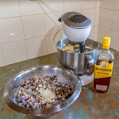 The cake-mixer is in action with the mixing bowl filled with batter. Next to the mixer is the large stainless steel bowl filled with dried fruits.