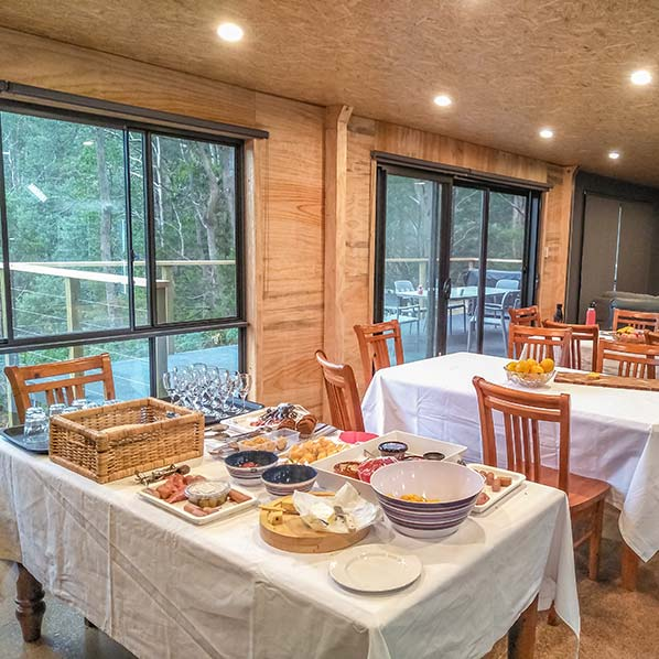 Inside the Barn showing a table set with food and the view out the large window to the wide deck and native bush.