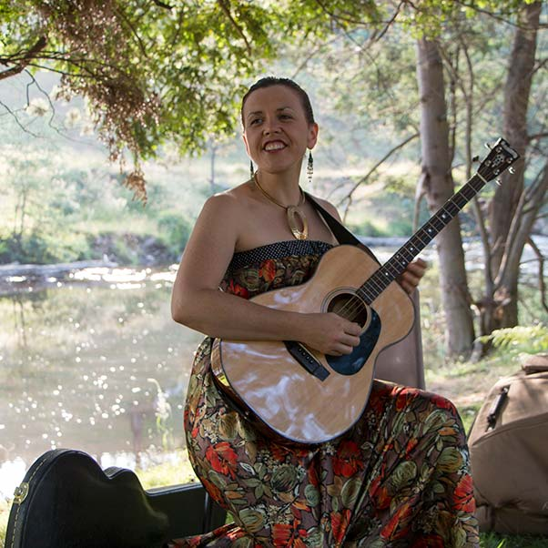 Liz Frencham playing guitar on the bank of the Ringarooma River at Tin Dragon Cottages.