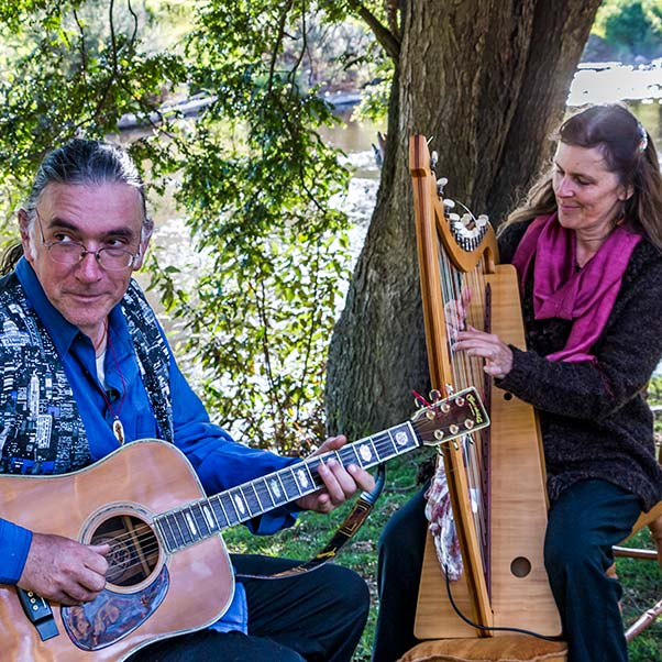 Frank playing guitar and Kate playing harp on the banks of the Ringarooma River at Tin Dragon Cottages.
