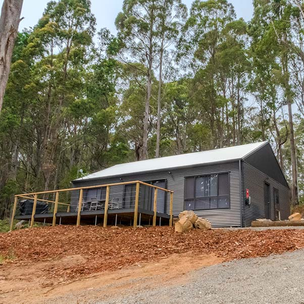 This charcoal coloured tin barn set in native bush has a large front deck. It is ideal for family holidays.
