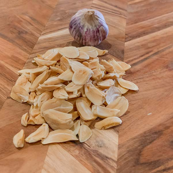A pile of dehydrated garlic bulbs are sitting on a wooden cutting board. This is one method to store garlic.