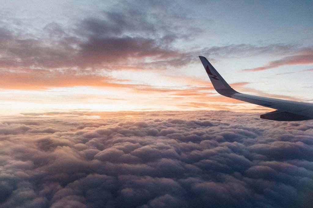 White airliner wing on top of a sea of clouds