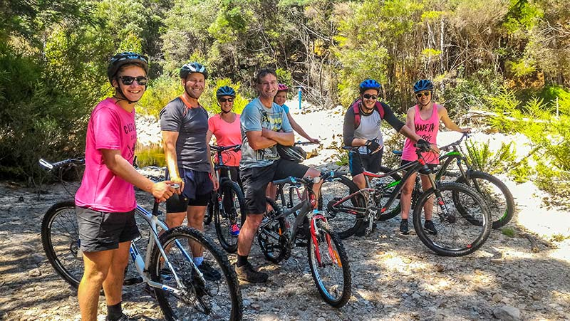 Group of friends with their mountain bikes smiling for the camera.
