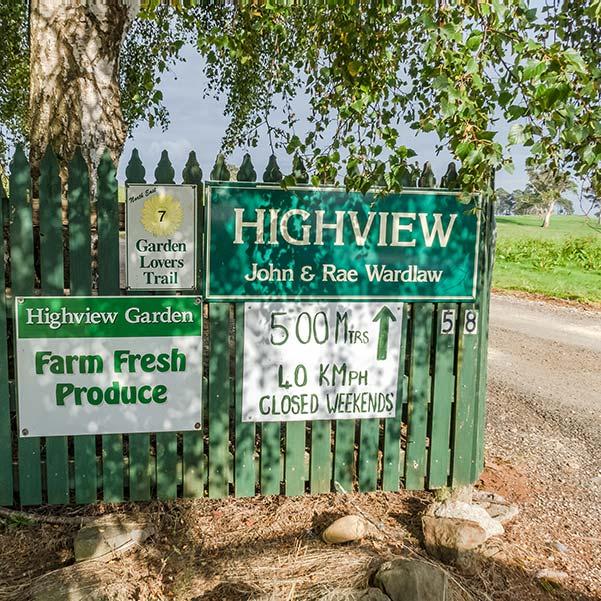 Green farm fence with signs advertising Highview fresh farm produce.