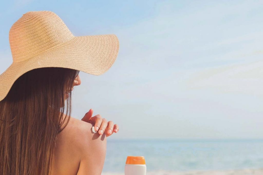 Woman at a beach with a large straw hat facing the ocean.