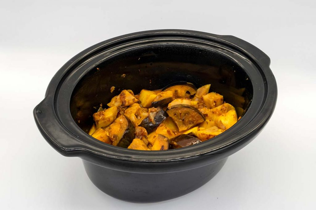 brinjal curry recipe being cooked in a ceramic crock pot