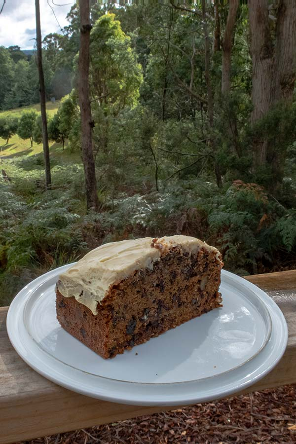 This iced carrot cake sitting on an outdoor table overlooking the garden and mountains is the result of my best ever carrot cake recipe.