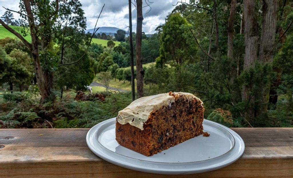 This is my best ever carrot cake placed on a balcony railing looking out towards the mountains in the distance.
