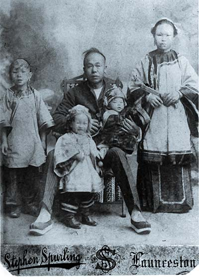 Ah Moy family wearing traditional dress for studio photo, late 1800s.