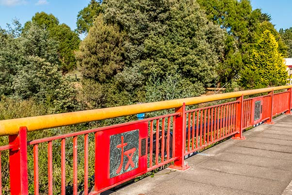 The red and gold Branxholm Bridge has Chinese calligraphy inspired icons to commemorate the towns Chinese history.