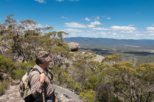 Graham is in the foreground looking out to a rock formation on the edge of an escarpment.