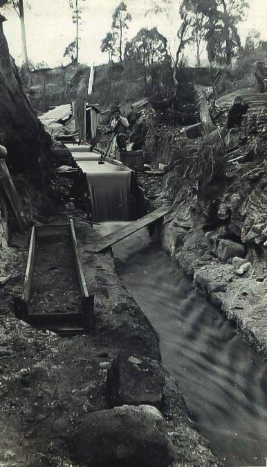 Water running from a water race through a sluice box with a Chinese miner standing adjacent.