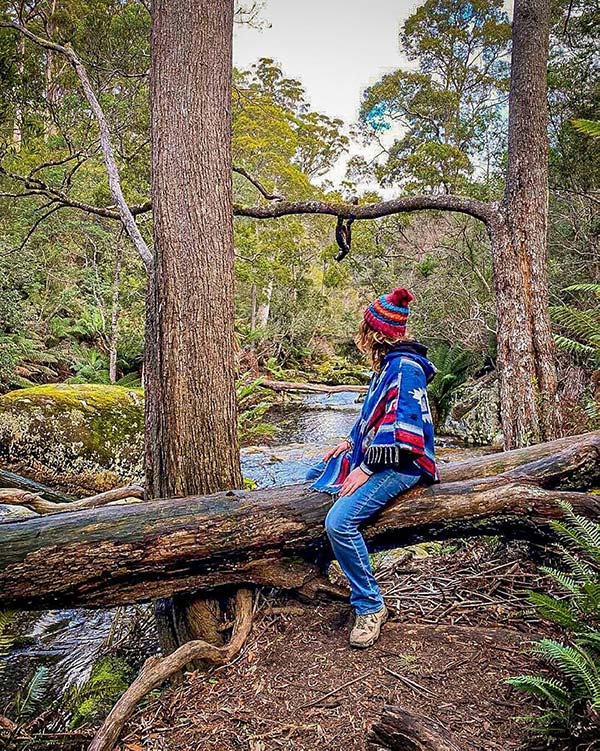 A woman wearing a blue poncho and red beanie is sitting on a fallen log and looking way from the camera towards a clear mountain stream near Halls Falls in Tasmania - from our road trip in Tasmania