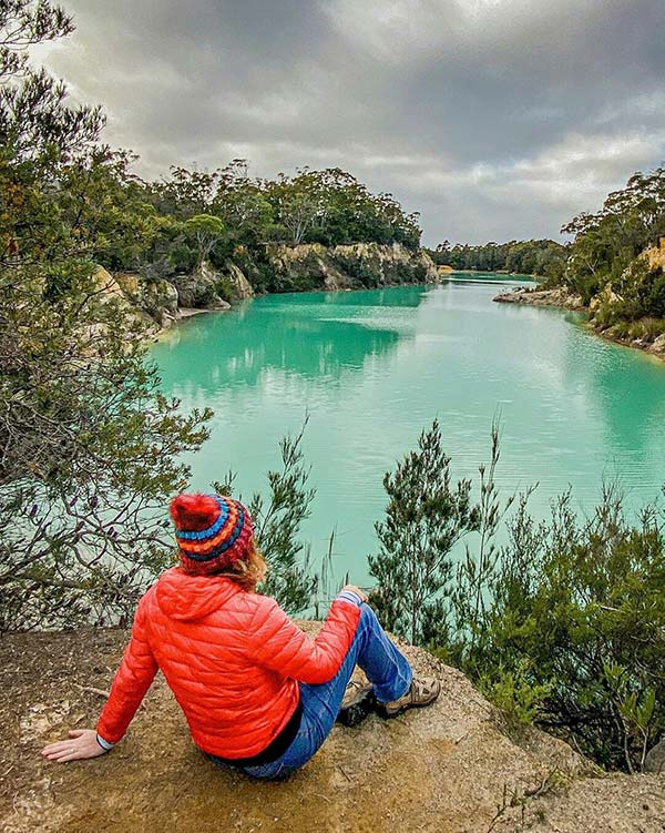 Woman wearing a red beanie and red coat sitting on a rock bank above the Little Blue Lake, South Mount Cameron in Tasmania