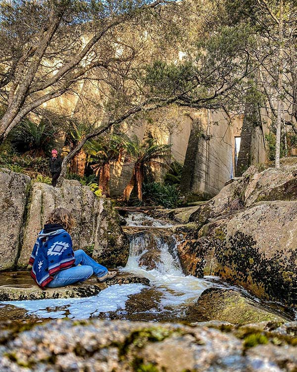 A woman wearing a blue poncho is sitting on a rock beside the Cascade River just below the face of the Mount Paris dam from our road trip in Tasmania