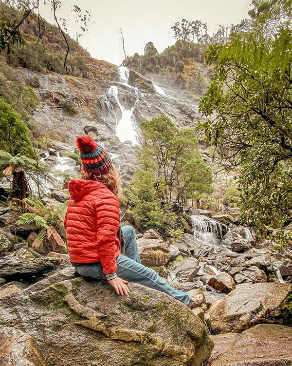 Woman wearing a red coat and red beanie is sitting on a rock just below the St Columba Falls on day one of her Tasmania road trip.