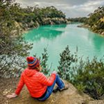 lady in a red coat and red beanie sitting above Little Blue Lake in North East Tasmania