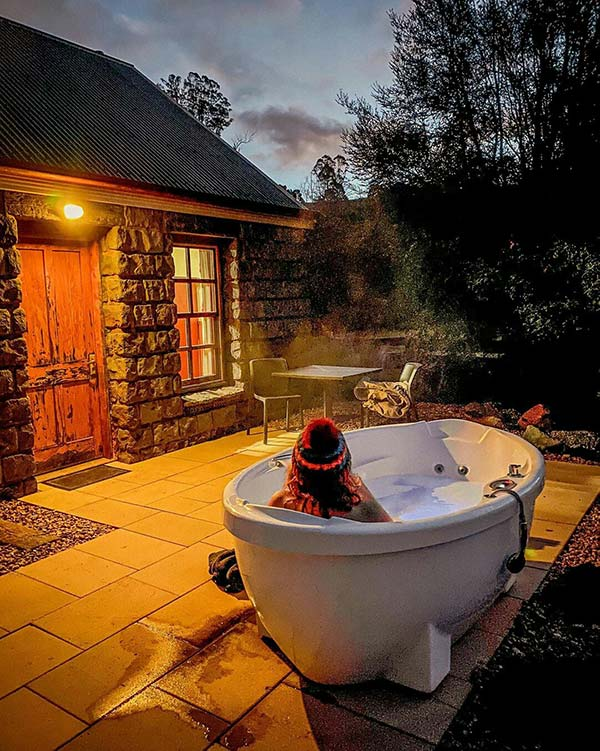 A woman wearing a red beanie is sitting in an outdoor hot spa, Ah Back cottage in Tasmania.